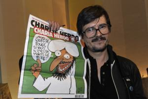 The Charlie Hebdo' s cartoonist Luz shows a special edition of French satirical magazine Charlie Hebdo, on November 3, 2011 during an editorial conference at the Theatre du Rond-point in Paris, one day after the offices of French satirical magazine Charlie Hebdo have been destroyed in a petrol bomb attack last night. The edition of the paper published yesterday, which was called Charia Hebdo - a play on the Islamic word sharia, was intended to