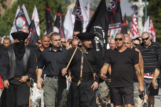 Devecser, 2012. augusztus 5. Demonstrálók vonulnak fel az Élni és élni hagyni - demonstráció a jogos magyar önvédelemért elnevezésû megmozduláson Devecserben 2012. augusztus 5-én. A Jobbik és több radikális szervezet részvételével megtartott demonstráció a katolikus templom elõtti téren kezdõdött, majd a résztvevõk felvonultak azokban az utcákban, ahol véleményük szerint cigányok laknak. A rendõrség kordonnal biztosította a felvonulók útvonalát. MTI Fotó: Nagy Lajos