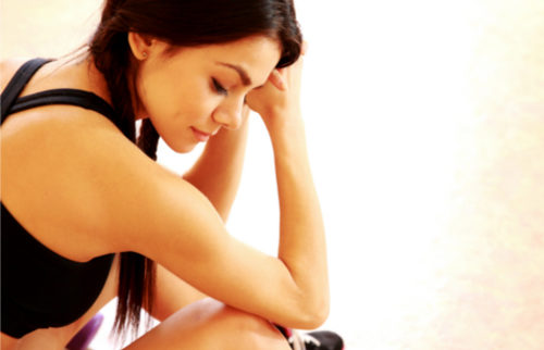 Young tired fit woman sitting on the floor at gym
