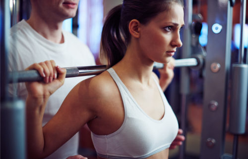 Young woman training with barbell in gym