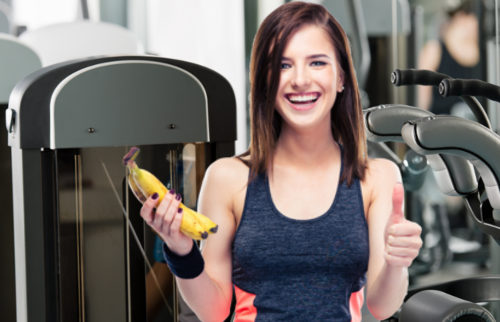 Young woman relax at the gym sitting on fitness machine