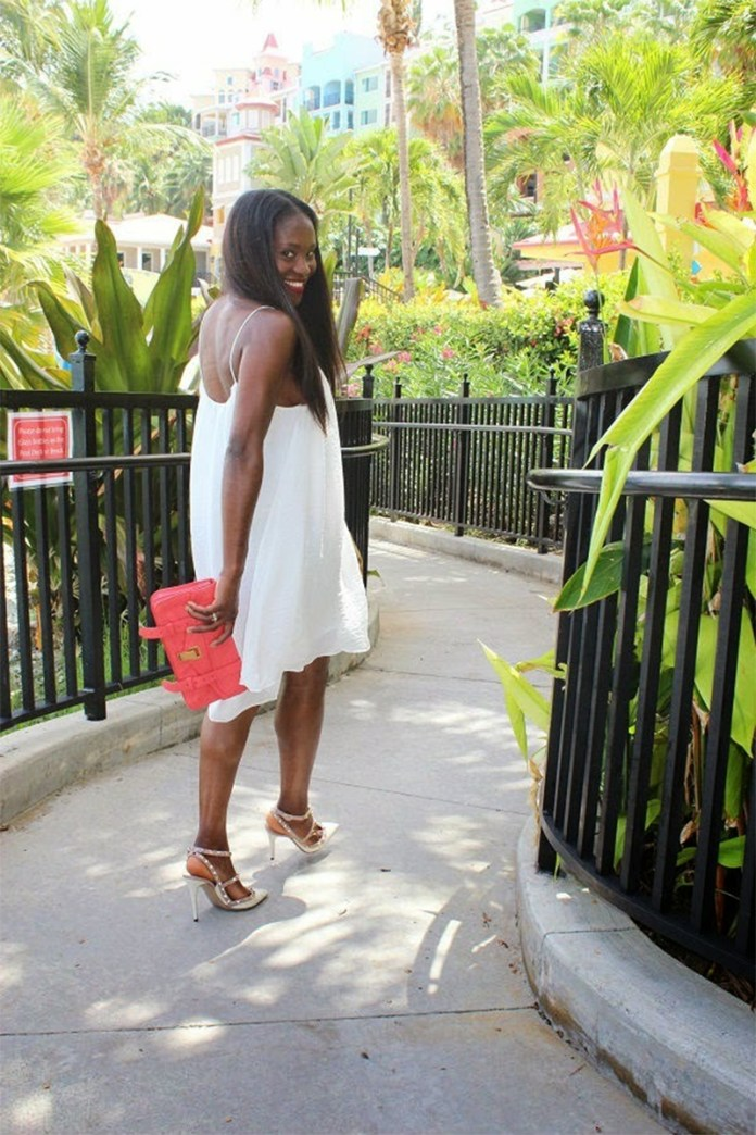 Ranti Onayemi wearing a white Just Female Swing Cami Dress with Valentino rockstud sandals and proenza schouler papaya clutch