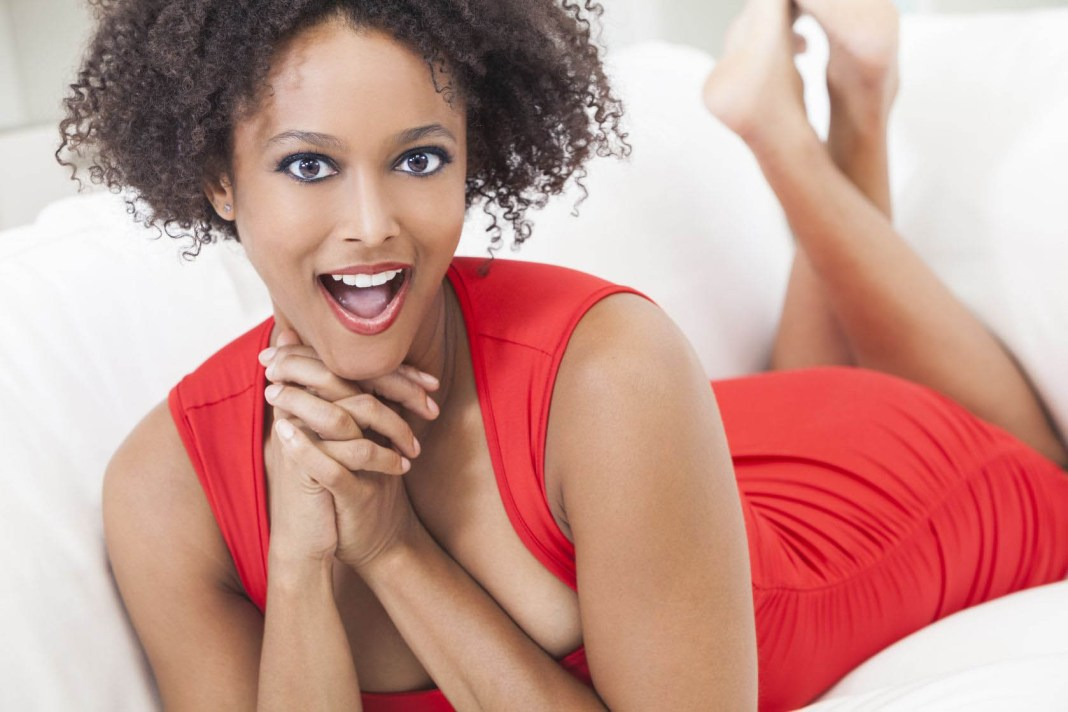 A beautiful mixed race African American girl or young woman laying down wearing a red dress looking happy and surprised