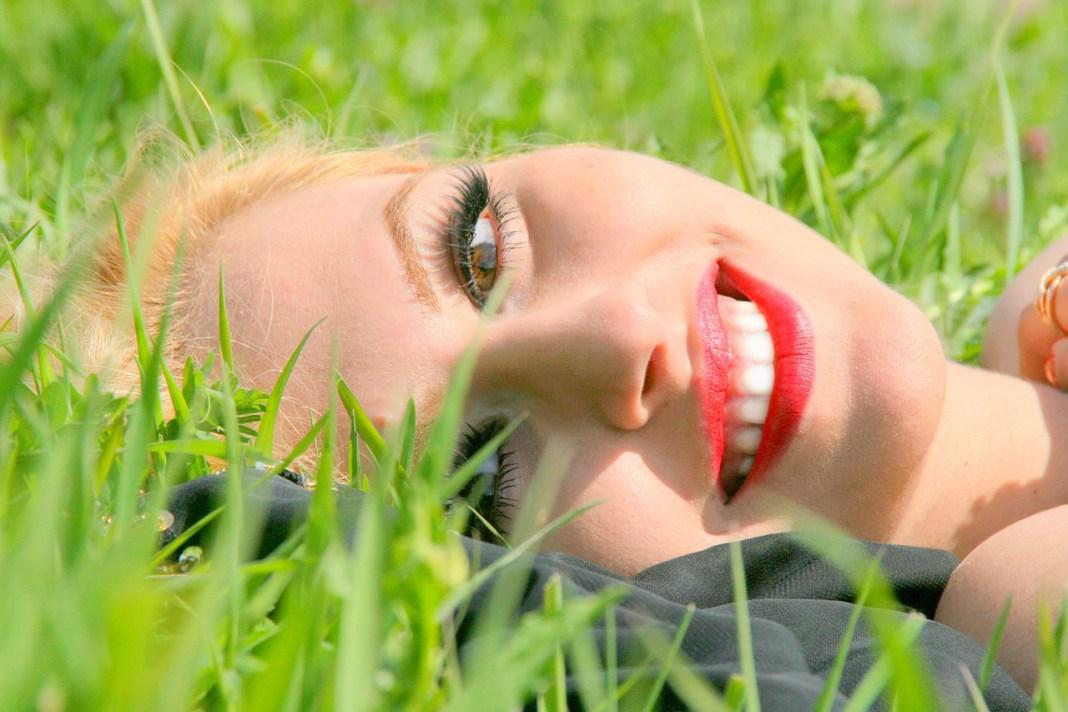 pretty girl smiling lying in grass