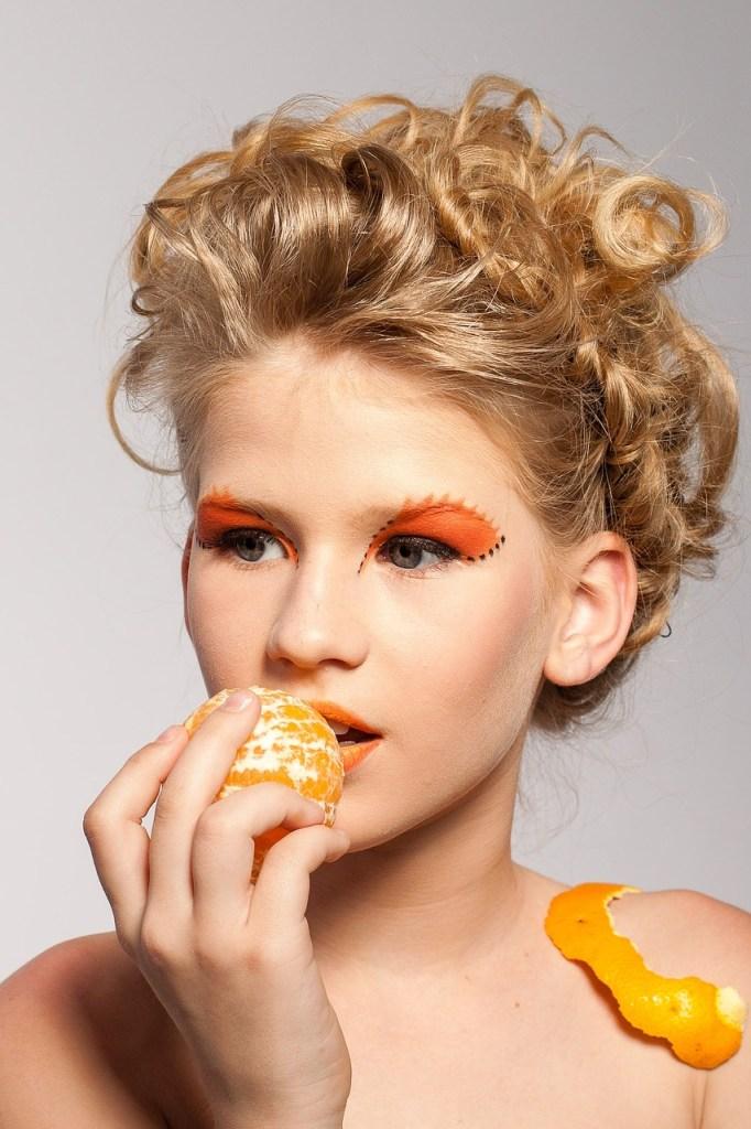 Pretty girl modeling pretend eating tangerine