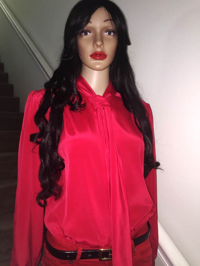 mannequin wearing red skinny jeans red blouse standing in front of stair case