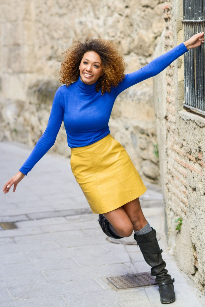 smiling curly hair woman wearing blue top yellow skirt outfit