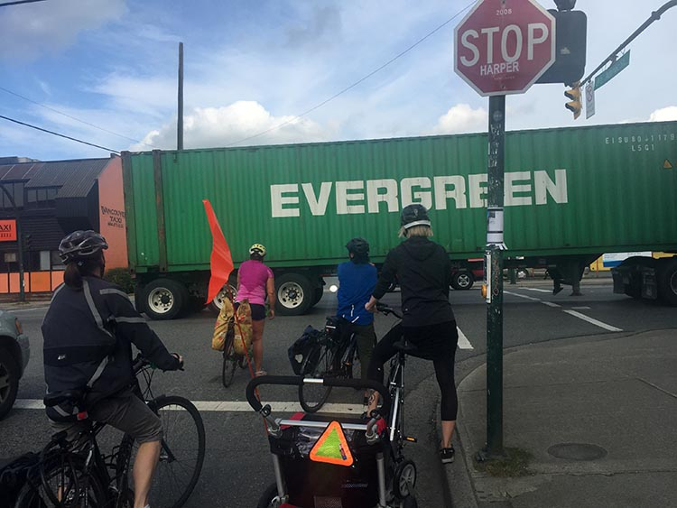 "Here's a mom I saw on Adanac Bike Route. They weren't in danger. But anyone who has been at this intersection knows how cars, trucks and bikes jostle for space. And I kind of love the irony in this photo. Mom towing tyke on bike, dwarfed by giant truck - and it's the TRUCK that's labeled ""Evergreen!"" The amazing evolution of Vancouver cycling infrastructure"