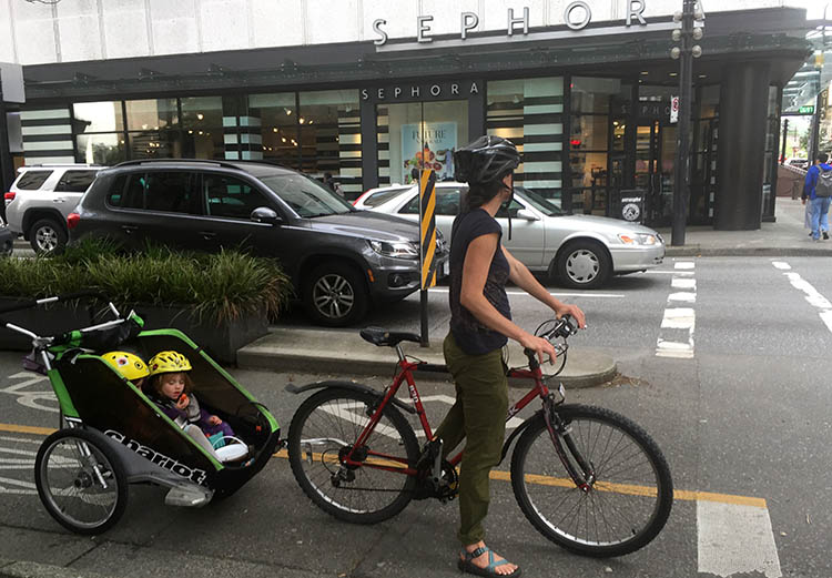 And here's another photo of a mom with two little kids on a separate bike lane on Dunsmuir Street, Vancouver. To me it is just painfully obvious that these little children need to be kept separate from cars that could kill them. And the research supports me - separate bike lanes are a WHOLE lot safer than mixing up bikes and cars