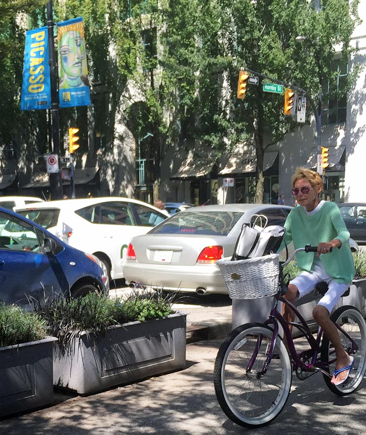 The Amazing Evolution of Vancouver Cycling Infrastructure. A woman riders her cruiser bike in relative peace and safety on the Hornby Street separated bike lane. The amazing evolution of Vancouver cycling infrastructure