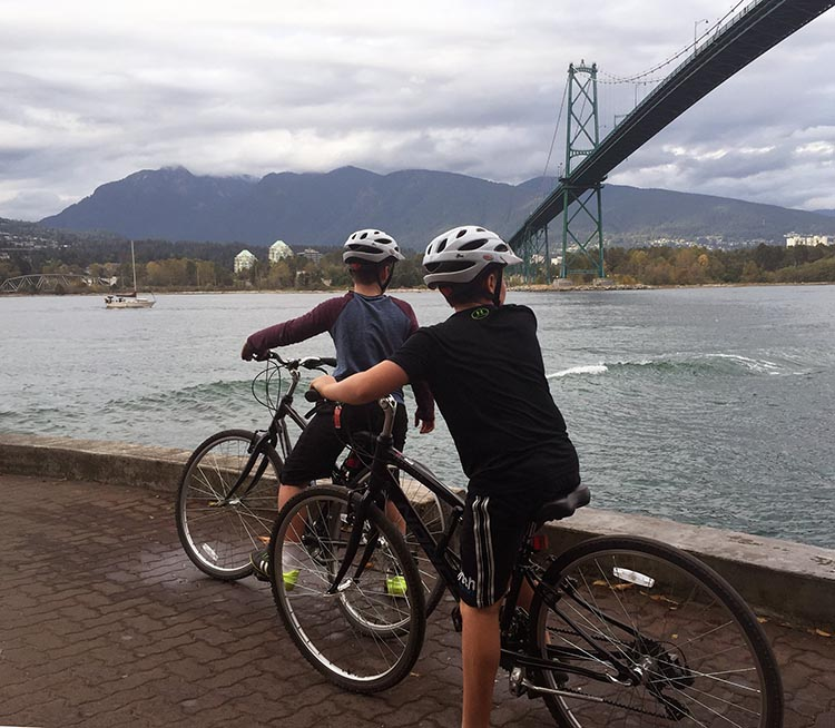 Two boys cycling on the Stanley Park bike trail in Vancouver. In this photo, they have stopped to watch the waves breaking onto the bike trail