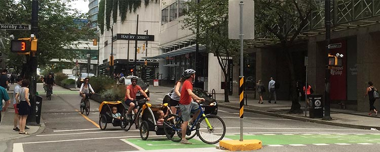 The Amazing Evolution of Vancouver Cycling Infrastructure. I have spotted many tourists towing children and babies with rented bikes on the separated bike lanes - such as this group, in the heart of Vancouver at the intersection of the Hornby and Dunsmuir separated bike lanes. The amazing evolution of Vancouver bike lanes