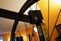 Each bike hangs by its front wheel from a rubberized rod