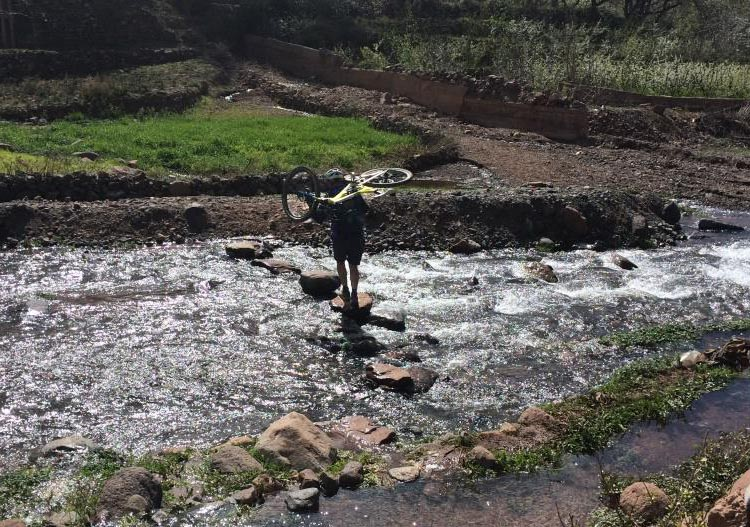 Cycling in the Atlas Mountains in Morocco. It is tricky to carry a bike while negotiating stepping stones across a river!