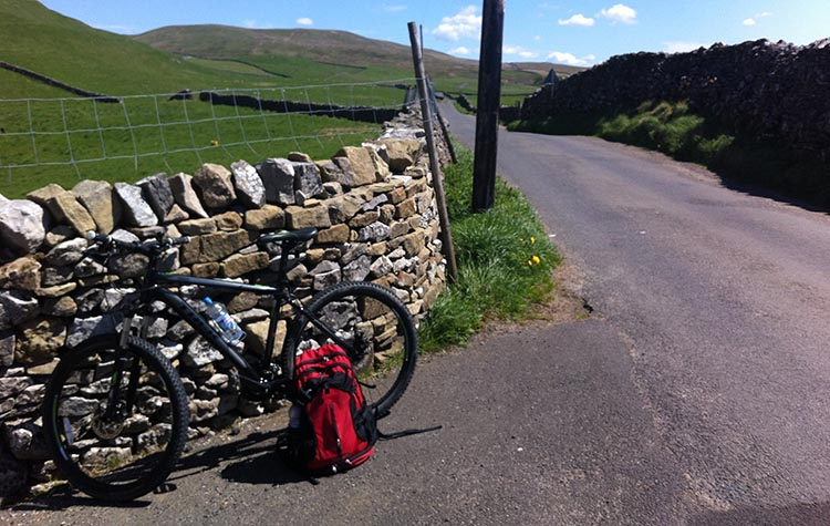 The Way of the Roses – Cycling Coast to Coast Across England bike next to fence and road