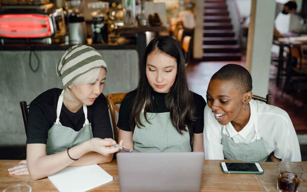 happy waitresses watching tutorials on laptop
