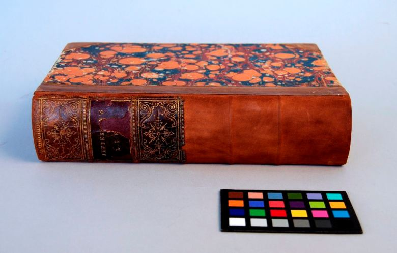 Image of brown calf binding with marbled paper sides, rebacked with top three spine panels readhered.