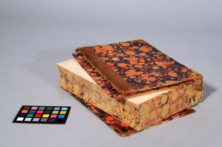 A brown calf binding with marbled sides and edges, showing right board, head, and foredge, with detached boards and endpaper