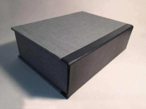 A closed grey cloth clamshell box with a blue leather spine