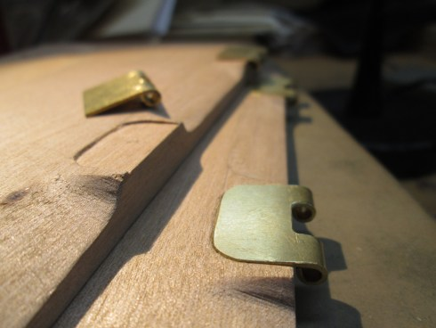 Closeup of shaped wooden board with inset brass clasps