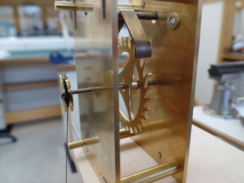 Closeup of a brass escapement with a toothed wheel and pallet, turned by a thread with a weight on the end.