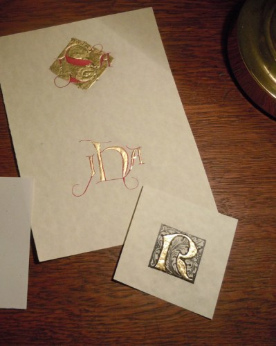 Image of two monograms, one with a raised and gilt diamond background with the initials in red, and the other outlined in red with the body of the letters filled with gilt gesso. A smaller piece of paper with a printed letter R is at the bottom, with the body of the letter also filled with gilt gesso.