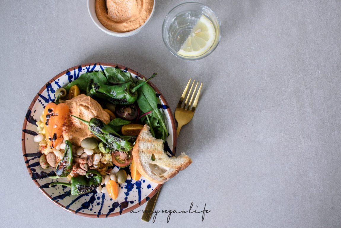 Tapas Bowl mit Pimientos de Padron, Safranreis und weißen Bohnen, dazu vegane Romesco-Sauce