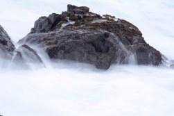 ocean rocks waves form waterfalls, white mist