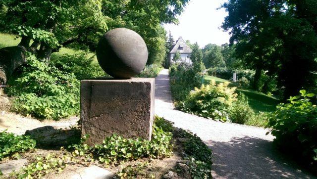 """Harmonie in Form und Schlichtheit - das von Goethe entworfene Denkmal """"Stein des Glücks"""" in seinem Garten an der Ilm. Im Hintergrund das Gartenhaus - Goethes erste Wohnung in Weimar ."""