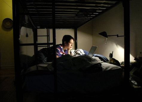 A boy plays games and does homework on his laptop (AP Photo/Noah Berger/File)