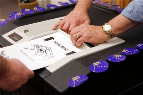 A ballot is inserted into a voting machine Tuesday, Nov. 2, 2010, in Girdwood, Alaska. (AP Photo/Ben Margot)