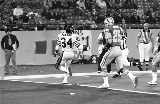 Chicago Bears Walter Payton (34) backs into the end zone and looks back at Detroit Lions Dick Jauron (26) in the fourth quarter of Thanksgiving Day game, Thursday, Nov. 24, 1977 in the Pontiac Silverdome. Chicago defeated the lions, 31-14. (AP Photo)