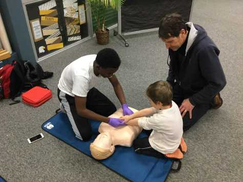 Sophomore Ayanle Issak, part of the Inver Hills EMR class, leads a CPR activity.