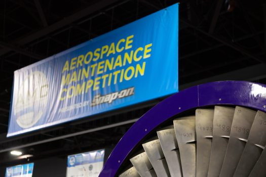 "A blue and yellow sign reading ""Aerospace Maintenance Competition"" with a jet engine in the foreground"