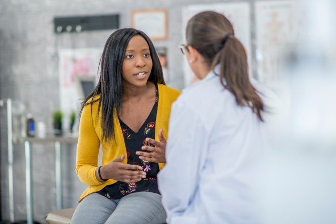 woman speaking with doctor in doctor's office