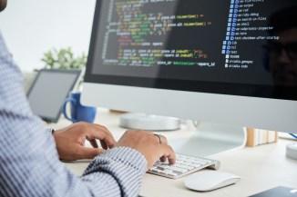 man coding on desktop computer
