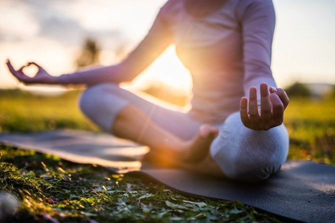 woman doing meditation at park during sunrise