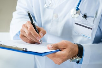 male doctor writing on medical chart
