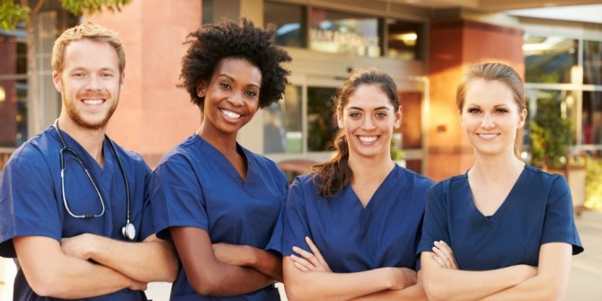 one man and three women wearing blue scrubs standing in a line with arms crossed and smiling