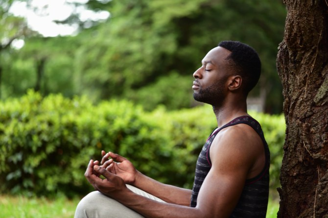 young-man-sitting-on-ground-against-tree-while-meditating-with-hands-resting-on-knees-cross-legged