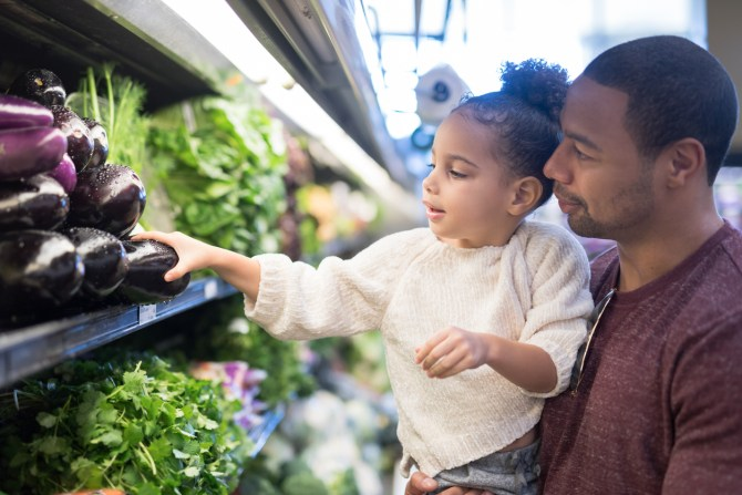 A pre-school age girl helps her dad pick out veggies in the produce section at the grocery store. He is holding her next to the produce and she is picking out eggplant.