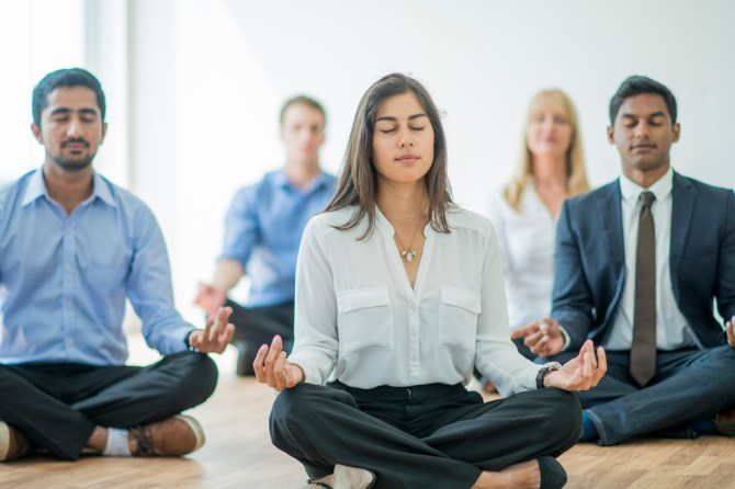 group-of-coworkers-sitting-cross-legged-with-eyes-closed-while-meditating-on-floor