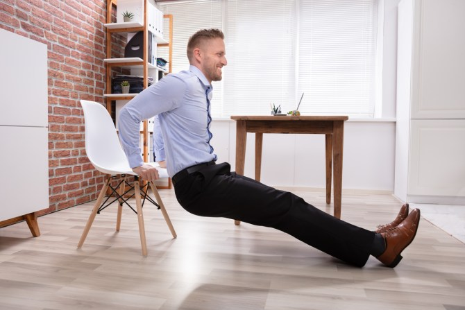 smiling-man-in-business-attire-doing-tricep-dips-in-office-with-white-chair