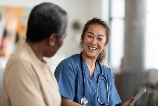 female-doctor-wearing-blue-scrubs-and-stethoscope-smiling-at-patient-in-the-foreground
