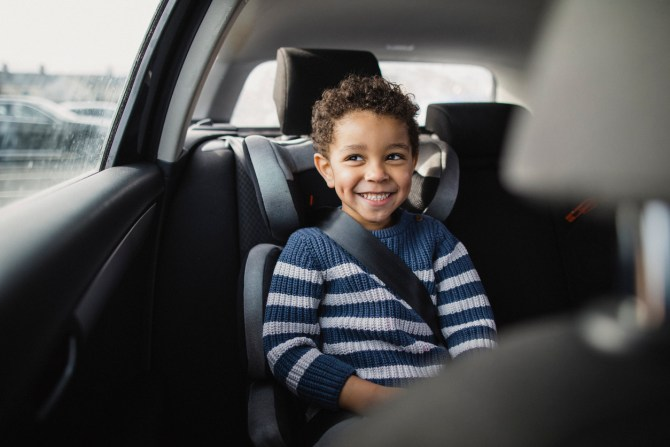 young-boy-smiling-while-sitting-in-car-seat-during-road-trip