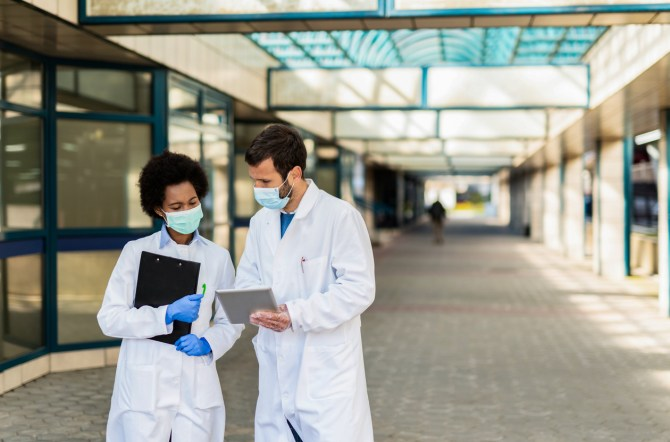 two-doctors-wearing-white-coats-and-face-masks-standing-in-outdoor-corridor-looking-at-tablet