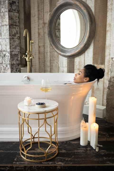 ethnic woman lying in bathtub in bathroom with candles