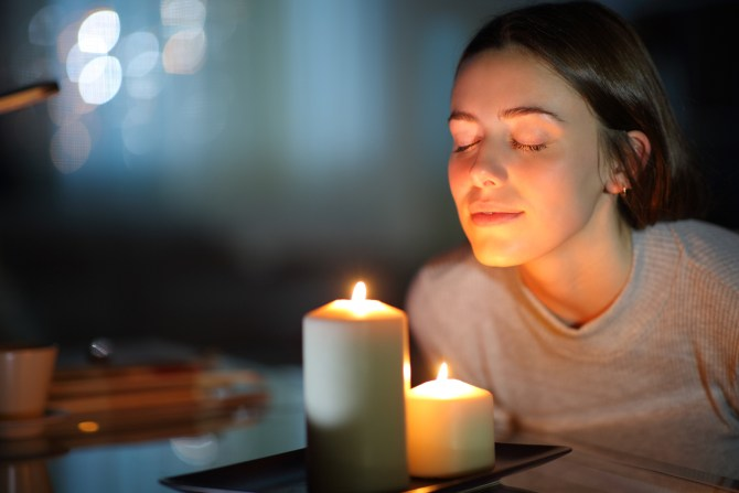 A woman leaning over two lit scented candles at night with her eyes closed to smell them.