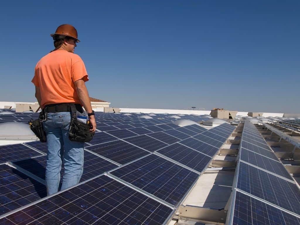 man inspecting solar panels on roof