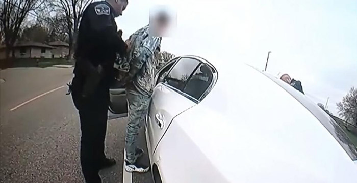 Black police officer attempting to put handcuffs on Daunte Wright with horrible technique.